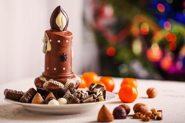 Bougie en chocolat sur fond de sapin de noël