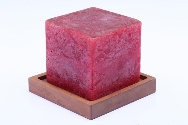Bougie cube en marbre rouge sur un support en bois de teck