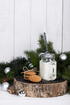 Bougie dans un bocal en verre et biscuits sur une bûche en bois près d'une branche d'épinette sur fond blanc.