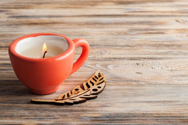 Bougie dans une tasse de corail sur une table en bois minable
