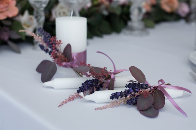 Bougie décorée de branches fraîches d'eucalyptus, d'astilbe et de lavande liées avec du ruban rose.