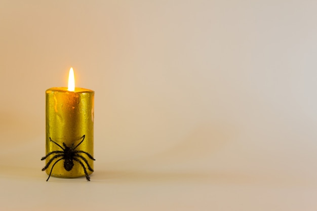 Bougie dorée avec un fond d'araignée halloween espace de copie minimal