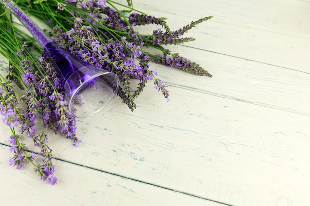 Bougie et fleurs de lavande sur bois blanc shaby
