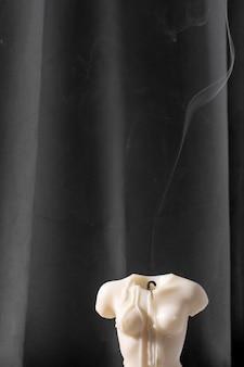 Bougie en forme de torse de femme brûlant dans un intérieur gris dans une atmosphère au ralenti et fumée après la bougie