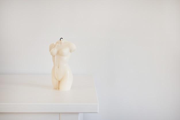 Bougie en forme de torse de femme dans une atmosphère moderne intérieure blanche et fond