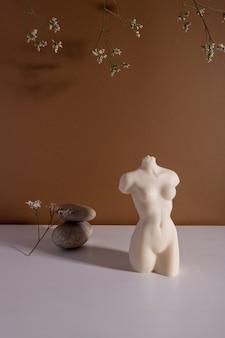 Bougie en forme de torse de femme à l'intérieur marron avec atmosphère d'automne en pierre et fleurs séchées