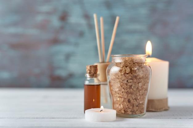 Bougie et huile de massage sur table blanche