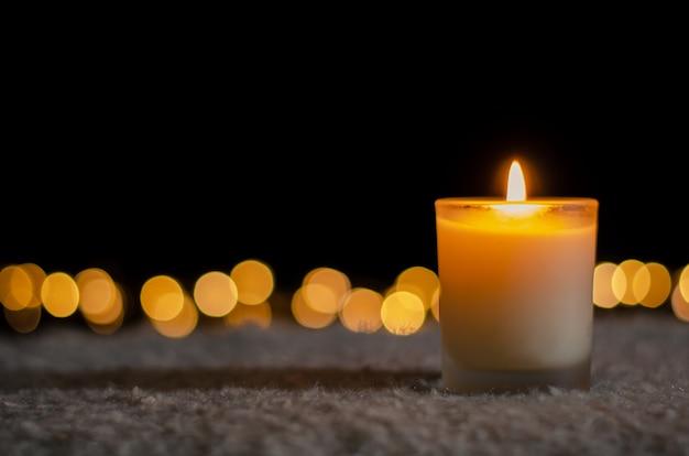 Bougie avec des lumières bokeh pour le concept de noël et du nouvel an.