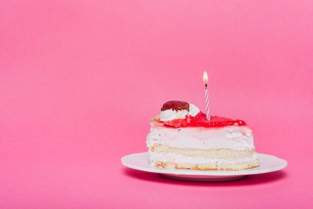 Bougie lumineuse sur la tranche de gâteau d'anniversaire avec fond rose