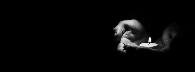 Bougie à la main brûlant sur le fond noir.