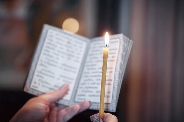 Bougie à la main et un livre de prières en gros plan dans l'église orthodoxe