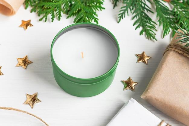 Bougie de noël avec des branches de sapin scintille et des cadeaux en forme d'étoile sur une table en bois