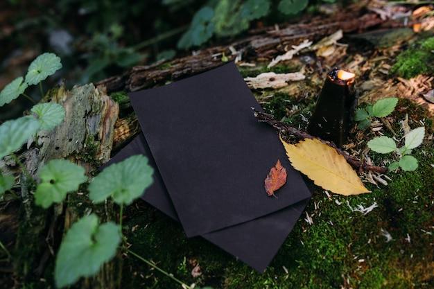 Bougie noire de maquette de papier d'artisanat noir sur fond de nature magique de forêt