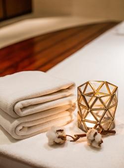 Bougie parfumée dans le salon de massage et détails de la branche de coton serviettes douces