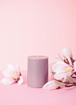 Bougie parfumée délicate fleur sur fond rose pastel