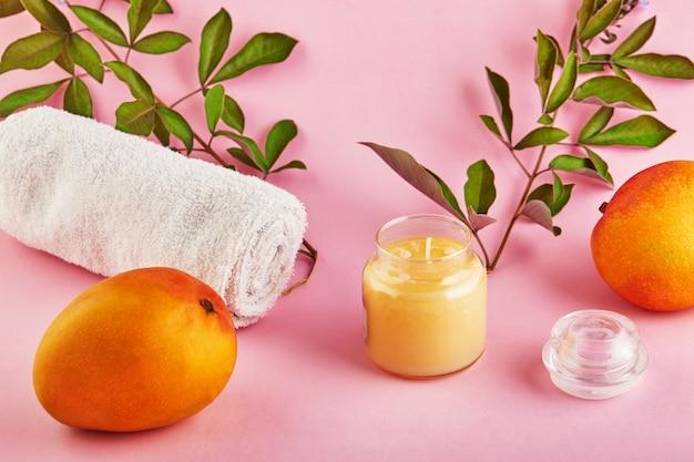 Bougie parfumée pour spa et maison avec un parfum de mangue et des feuilles vertes sur un espace rose.
