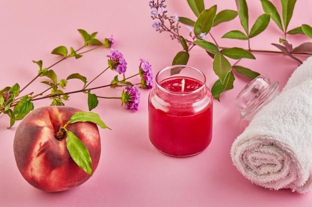 Bougie parfumée pour spa et maison avec parfum de pêche et feuilles vertes sur un espace rose.