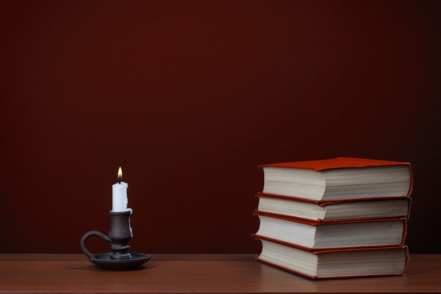 Bougie et pile de livres rouges sur table sur fond rouge. histoire d'horreur