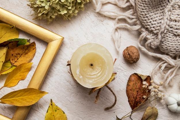 Bougie à plat avec feuilles mortes, hortensia sec, pull. concept confortable d'automne