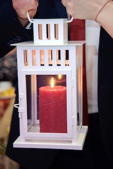Bougie rouge allumée dans la lanterne blanche