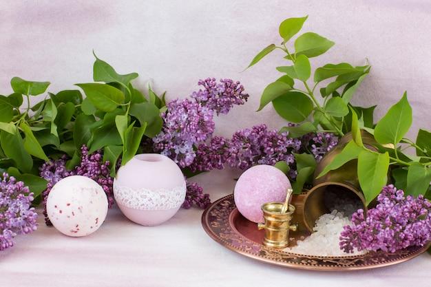 Bougie, savon, sel de bain dans un pichet en or et branches de lilas
