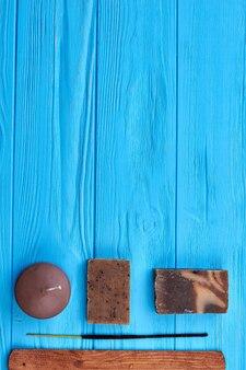 Bougie vue de dessus à tir vertical avec savon et bâton. fond de bureau en bois bleu.
