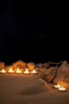 Des bougies allumées autour de la petite tombe comme mémoire sur une surface sombre