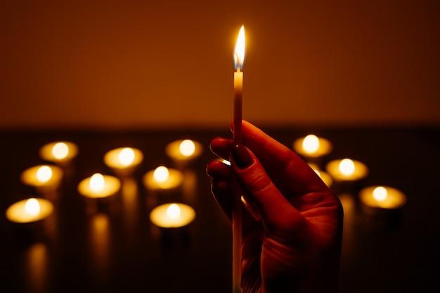 Des bougies allumées. bougie dans des mains féminines. beaucoup de bougies qui brûlent la nuit. de nombreuses flammes de bougies brillent.