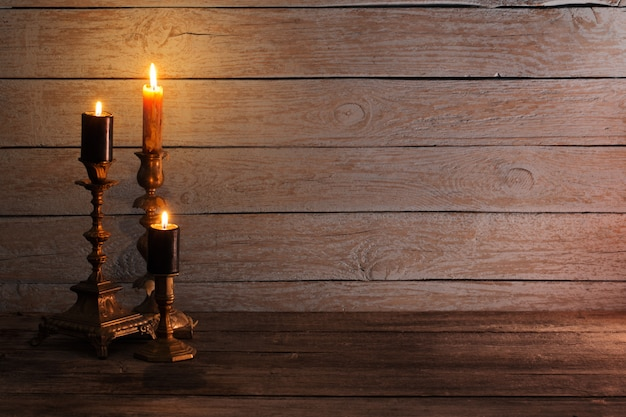 Des bougies allumées en chandeliers sur fond de bois ancien