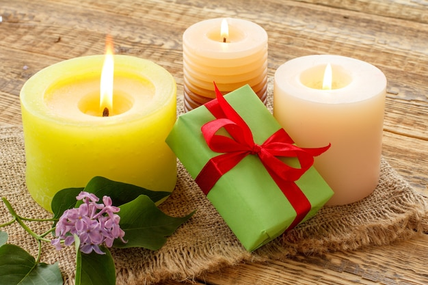 Bougies allumées, coffret cadeau et fleurs lilas sur un sac et de vieilles planches de bois.