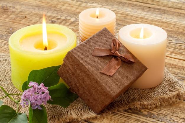 Bougies allumées et coffret cadeau marron sur un sac et de vieilles planches en bois. vue de dessus.