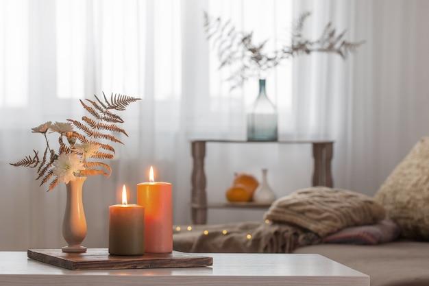 Bougies allumées avec décor d'automne sur table blanche à la maison