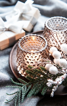 Bougies allumées décoratives de noël, branche de sapin et coffrets cadeaux sur une surface en laine grise