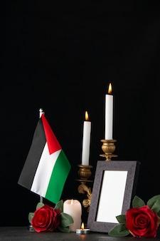 Bougies allumées avec drapeau palestinien et fleurs sur la surface sombre