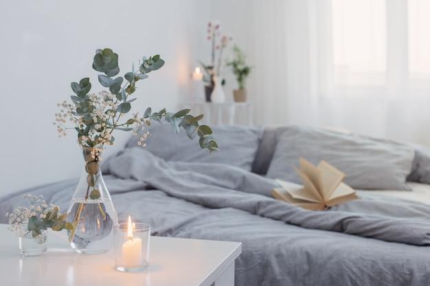 Des bougies allumées et de l'eucalyptus dans un vase en verre dans une chambre blanche