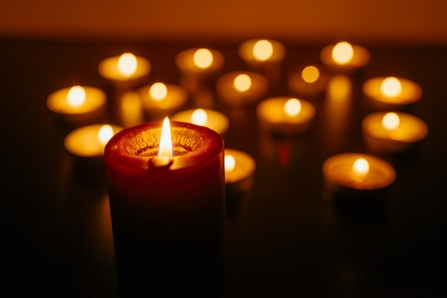 Des bougies allumées. faible profondeur de champ. beaucoup de bougies de noël qui brûlent la nuit. de nombreuses flammes de bougies brillent.
