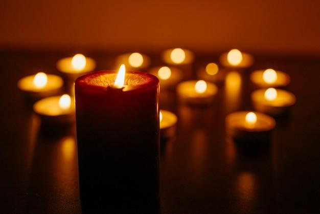 Des bougies allumées. faible profondeur de champ. beaucoup de bougies qui brûlent la nuit. de nombreuses flammes de bougies brillent.