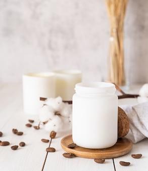 Bougies allumées avec des fleurs de coton et des grains de café sur une surface en bois blanche
