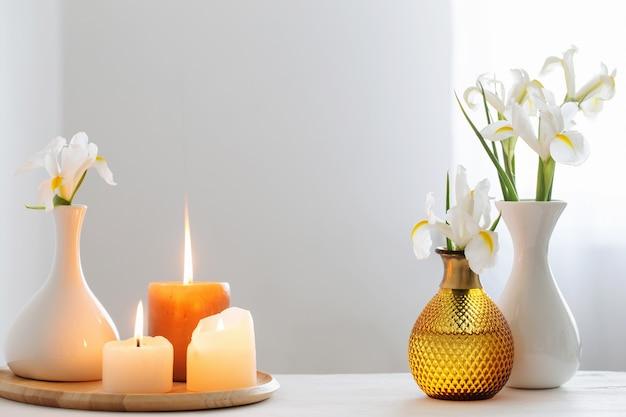 Des bougies allumées et des fleurs de printemps sur une étagère en bois à l'intérieur blanc