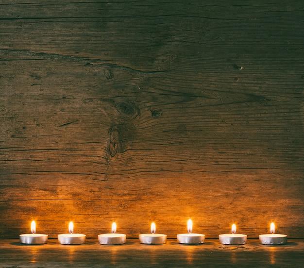 Des bougies allumées sur le fond d'un vieux plateau de grange