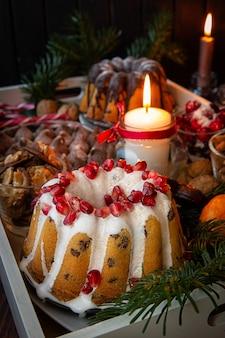 Bougies allumées, gâteau à la grenade et une variété de bonbons