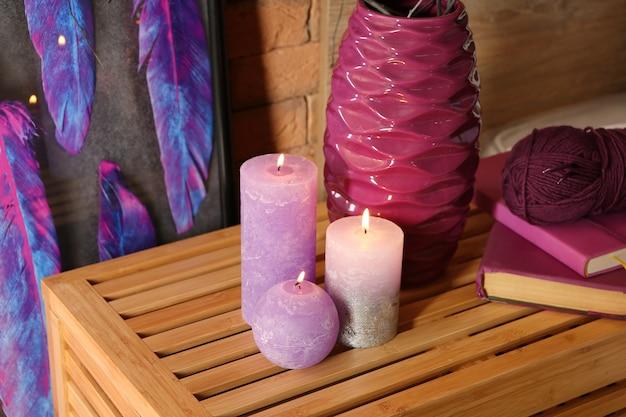 Des bougies allumées avec des livres et du fil à tricoter sur une table en bois