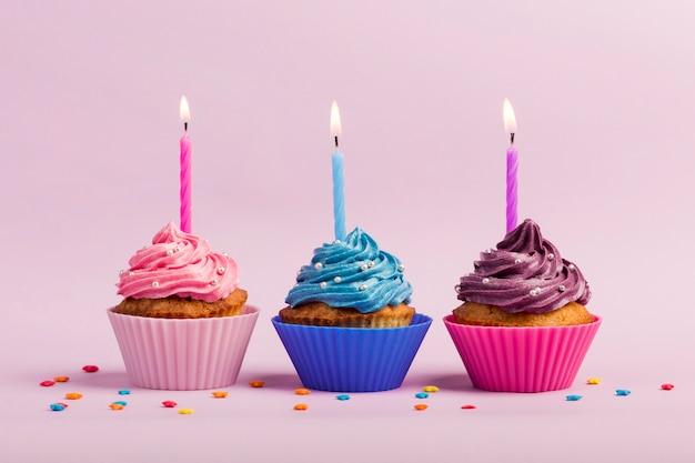 Bougies allumées sur les muffins avec pépites colorées sur fond rose