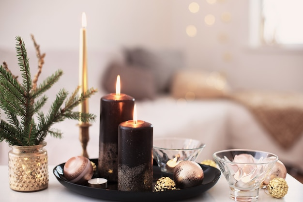 Bougies allumées noires avec des boules de noël à l'intérieur blanc