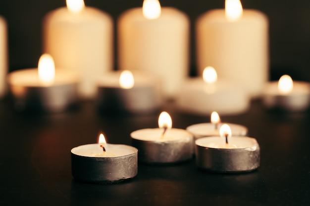 Bougies allumées la nuit. bougies blanches brûlant dans l'obscurité