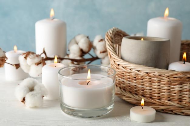 Bougies allumées, panier et coton sur bois blanc, gros plan