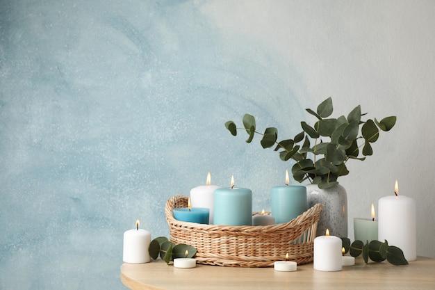 Bougies allumées, panier et vase avec eucalyptus sur bleu