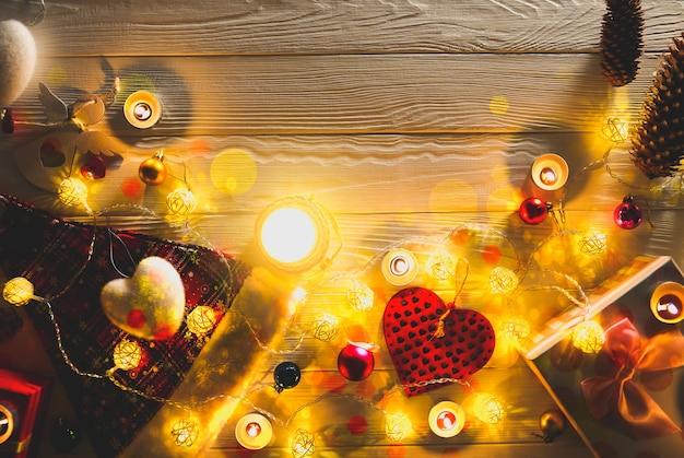 Des bougies allumées parmi de belles lumières de noël et des décorations de guirlandes. fond de fête du nouvel an. cadeaux, cadeaux, carte postale de voeux pour les vacances d'hiver.
