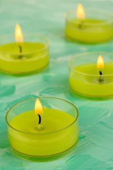 Bougies allumées avec des perles sur fond vert