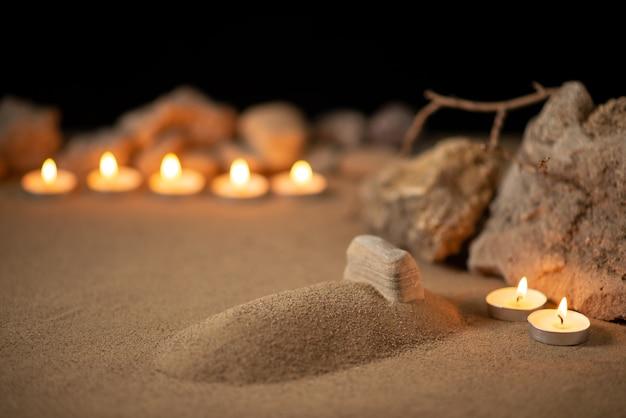 Bougies allumées avec petite tombe sur une surface sombre